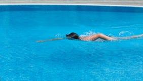 Ein Junge schwimmt in einem Pool. Seitenansicht Lizenzfreies Stockfoto