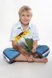 Ein Junge sitzt auf einem Fußboden mit einer Sonnenblume in den Händen. Er ist glücklich. Lizenzfreie Stockfotografie