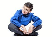 Ein Junge sitzt und liest ein Buch Stockbilder
