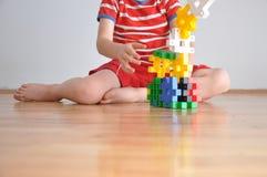 Ein Junge spielt mit Spielwarenwürfeln Lizenzfreie Stockbilder