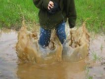 Ein Junge springt in eine schlammige Pfütze lizenzfreie stockfotos