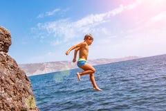 Ein Junge springt von der Klippe in das Meer an einem heißen Sommertag Feiertage auf dem Strand Das Konzept des aktiven Tourismus lizenzfreie stockfotos