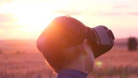 Ein Junge steht auf einem Weizengebiet bei Sonnenuntergang in den virtuellen Gläsern stock video