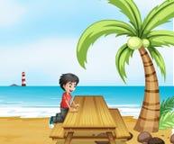 Ein Junge am Strand mit einem Holztisch nahe dem Kokosnussbaum Lizenzfreies Stockfoto