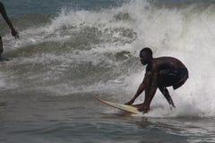 Ein Junge surfen die Wellen in Lagos-Strand, Bewunderer schauen an lizenzfreies stockbild