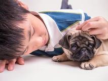 Ein Junge tröstet einen traurigen Welpen Lizenzfreies Stockfoto