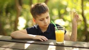 Ein Junge trinkt Orangensaft an einem Tisch in der Natur Ein Junge trinkt Orangensaft draußen stock footage