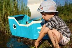 Ein Junge und ein behelfsmäßiges Schiff mit einem Segel auf dem Ufer Lizenzfreie Stockfotografie