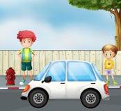 Ein Junge und ein Kind an der Straße mit einem Auto Lizenzfreie Stockfotos