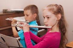 Ein Junge und ein Mädchen, welche die Flöte spielen Lizenzfreie Stockfotos