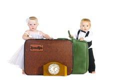 Ein Junge und ein Mädchen stehen nahes Gepäck Stockbild
