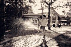 Ein Junge und ein Spray des Wassers Stockbilder