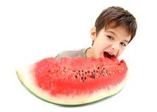 Ein Junge und eine Scheibe der Wassermelone Lizenzfreie Stockfotos
