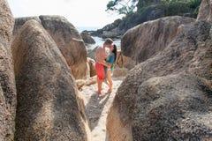 Ein Junge und langhaariger ein Mädchen Brunette, die unter den großen Steinen auf dem Strand küssen Lizenzfreies Stockbild