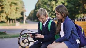Ein Junge und ein Mädchen benutzen einen Smartphone stock video