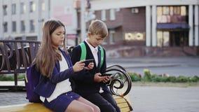 Ein Junge und ein Mädchen benutzen einen Smartphone und eine Tablette stock footage