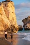 Ein Junge und ein Mädchenspaziergang barfuß am Strand againt die PETRA-tou Romiou-Geburtsortfelsen der Aphrodite gebadet im Nachm lizenzfreies stockfoto