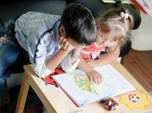 Ein Junge und seine Schwester lesen ein Buch stockbild
