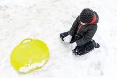 Ein Junge von sieben Jahren alten Sitzen auf dem Schnee und ein grüner Plastikuntertassenschlitten, der nahe ihm liegt Konzept vo lizenzfreie stockfotografie