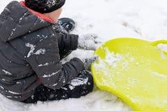 Ein Junge von sieben Jahren alten Sitzen auf dem Schnee und ein grüner Plastikuntertassenschlitten, der nahe ihm liegt Konzept vo stockfotografie