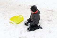 Ein Junge von sieben Jahren alten Sitzen auf dem Schnee und ein grüner Plastikuntertassenschlitten, der nahe ihm liegt Konzept vo lizenzfreie stockfotos