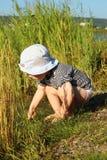 Ein Junge von zwei Jahren auf dem Ufer von einem See Lizenzfreie Stockfotos