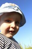 Ein Junge von zwei Jahren lächelt gegen den Himmel Lizenzfreies Stockbild