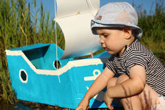 Ein Junge von zwei Jahren und ein selbst gemacht Schiff mit einem Segel Lizenzfreie Stockfotografie
