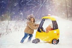 Ein Junge in weißem, verschneiter Winter im Wald stockbild