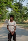 Ein Junge wirft für ein Foto beim In Herden leben des Viehs außerhalb Bhadarsa auf stockfotografie