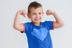 Ein Junge zeigt die Muskeln in ihren Armen Lizenzfreies Stockfoto