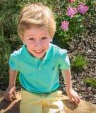 Ein Junge zeigt Glück, während er den Anblick an einem allgemeinen Garten erforscht Stockfotos