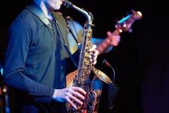 Ein Jungekerl spielt ein Saxophon mit einem Mikrofon stockfoto