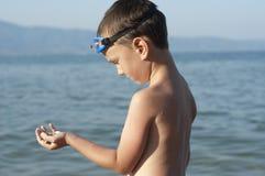 Ein Jungenblick auf Felsen, die er am Strand pucked Stockfotos