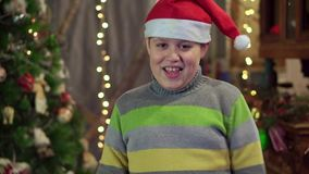 Ein Jungenjugendlicher in einem Hut Santa Claus tanzt nahe dem Weihnachtsbaum Weihnachtsfeiertag, guten Rutsch ins Neue Jahr stock footage