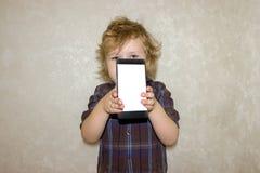 Ein Jungenkind untersucht die Kamera eines Smartphone, zeigt den Schirm mit seinem digitalen Foto lizenzfreies stockbild