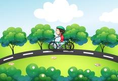 Ein Jungenreiten in seinem Fahrrad an der Straße Stockfotos