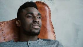 Ein junger afrikanischer Mann, der im Stuhl sitzt, den Abstand untersucht und an etwas denkt Mann schaut durchdacht Stockbild