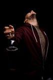 Ein junger Alkoholiker in einer Haube auf einem schwarzen Hintergrund Ein betrunkener erwachsener Junge mit einer Flasche Bier Al Lizenzfreies Stockbild