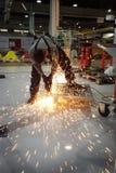 Ein junger Arbeitnehmer schneidet ein Metalldetail in einem Raum lizenzfreie stockfotos
