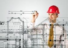 Ein junger Architekt, der einen Hausplan zeichnet Stockbilder