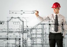 Ein junger Architekt, der einen Hausplan zeichnet Lizenzfreies Stockbild