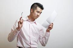 Ein junger asiatischer Mann, der einen Brief liest Stockbild