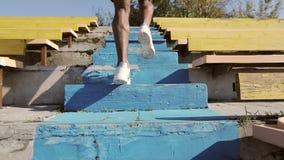 Ein junger Athlet läuft schnell herauf die Treppe im Stadion stock video footage