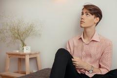 Ein junger attraktiver Mann in einem gestreiften Hemd und in schwarzen Jeans sitzt zuhause mit einem Smartphone und meditiert Das lizenzfreie stockfotografie