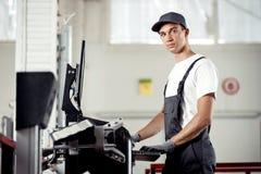 Ein junger Automechaniker in der Uniform ist Abfertigungscomputer, der nach Wanzen in einem Automotor sucht stockfotografie