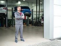 Ein junger Automechaniker mit einem Schlüssel in seinen Händen Lizenzfreie Stockbilder