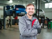 Ein junger Automechaniker mit einem Schlüssel in seinen Händen Lizenzfreies Stockbild