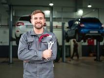 Ein junger Automechaniker mit einem Schlüssel in seinen Händen Lizenzfreies Stockfoto