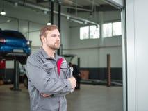 Ein junger Automechaniker mit einem Schlüssel in seinen Händen Stockfotos
